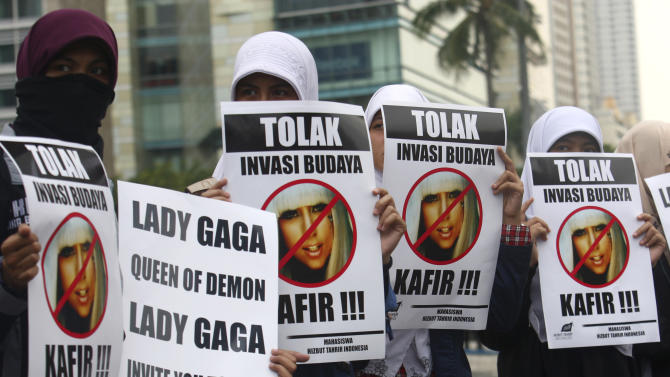 "Muslim women hold posters during a protest against Lady Gaga's concert that is scheduled for June 3, in Jakarta, Indonesia, Thursday, May 24, 2012. Lady Gaga might have to cancel her sold-out show in Indonesia because police worry her sexy clothes and dance moves undermine Islamic values and will corrupt the country's youth. The writings on the posters read ""Reject cultural invasion"" and ""Infidel."" (AP Photo/Tatan Syuflana)"