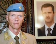 """UN top observer Major General Robert Mood stands next to a portrait of Syrian President Bashar al-Assad upon his arrival in Damascus in April. Mood said on Wednesday he was """"deeply disturbed"""" by a newly discovered massacre in Syria, as the opposition insisted Assad must step down if a peace plan is to be saved"""