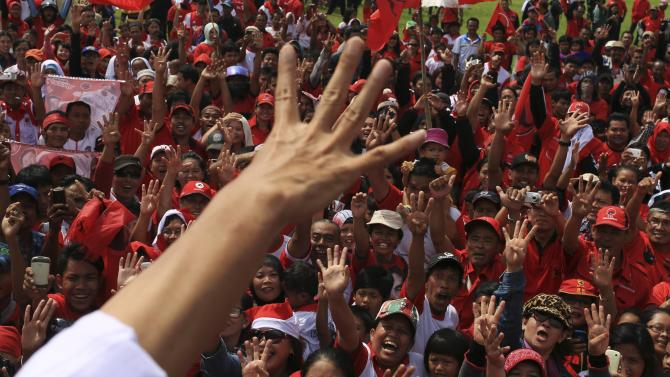 Supporters gesture along with Jakarta governor and presidential candidate Widodo during a campaign in Jakarta
