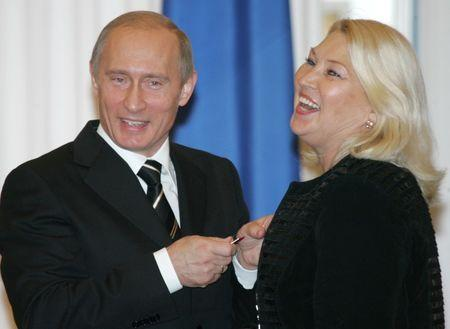 Russian President Putin shares a joke with the head coach of the Russian syncronized swimming team Pokrovskaya while giving her a state award at the Yekaterininsky Hall of the Kremlin in Moscow during the State Awards handing ceremony