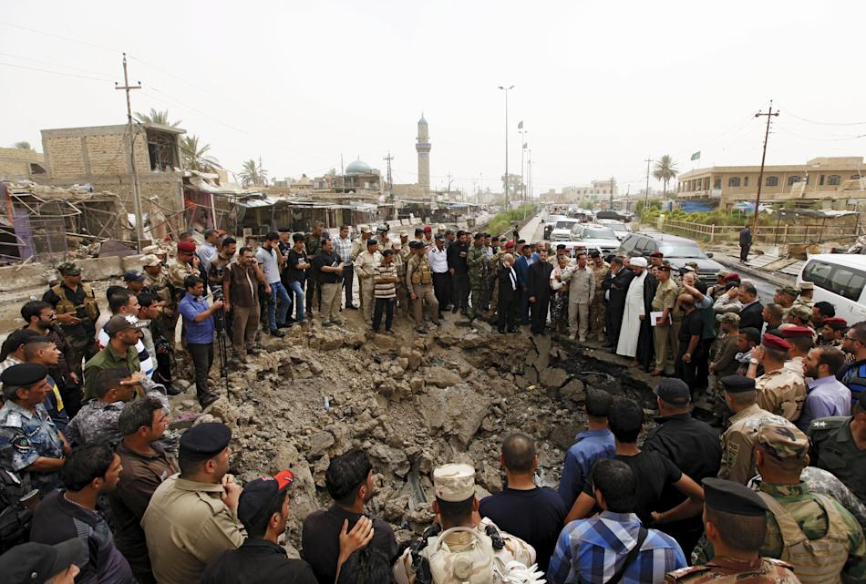 Residents and Iraqi security forces gather around a hole caused by a suicide car attack at a market in Khan Bani Saad, northeast of Baghdad