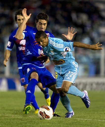Argentina's Tigre's Diego Ferreira, left, fights for the ball with Peru's Sporting Cristal's William Chiroque at a Copa Libertadores soccer match in Buenos Aires, Argentina, Tuesday, April 9, 2013