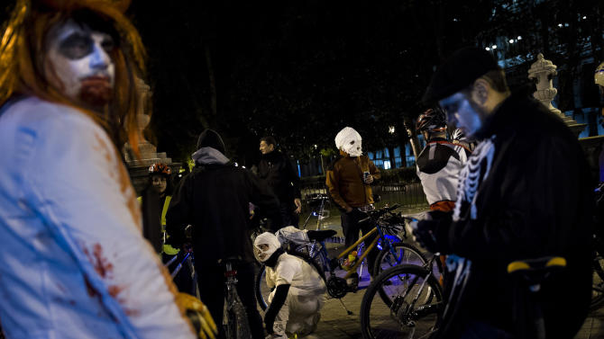 "People, most of them dressed with Halloween costumes, take part in the flash mob ""Halloween bike ride""  before touring around the city in Madrid, Tuesday, Oct. 31, 2012.  (AP Photo/Daniel Ochoa de Olza)"