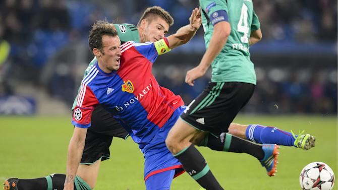 Basel's Marco Streller, center, fights for the ball against Schalke's Roman Neustaedter, background, during the Champions League group E group stage soccer match between Switzerland's FC Basel and Germany's FC Schalke 04 at the St. Jakob-Park stadium in Basel, Switzerland, Tuesday, Oct. 1, 2013
