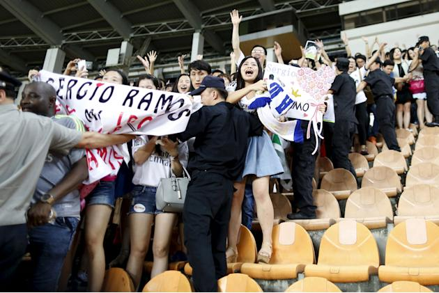 Real Madrid fans react during the team's training session at Tianhe Stadium in the southern Chinese city of Guangzhou