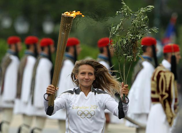 A torchbearer runs with the Olympic flame during a ceremony at Panathenaean stadium in Athens, Thursday, May 17, 2012. The torch begins its 70-day journey to arrive at the opening ceremony of the Lond