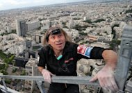 "French ""Spiderman"" Alain Robert, pictured here climbing Paris' First Tower in May, added another structure to his record of climbing achievements on Saturday, scaling most of a 388-metre (1,280-foot) tower in central China"