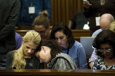 Aimee Pistorius, sister of Olympic and Paralympic track star Oscar, rests her head on an unidentified woman's shoulder during the fifth day of his trial for the murder of his girlfriend Reeva Steenkamp at the North Gauteng High Court in Pretoria
