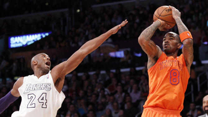 New York Knicks' J.R. Smith scores over Los Angeles Lakers' Kobe Bryant during the first half of their NBA basketball game in Los Angeles