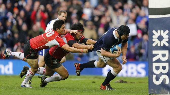 Scotland's Alasdair Dickinson scores a try against Japan as Kosei Ono and Shota Horie attempt to tackle him during their rugby union match at Murrayfield Stadium in Edinburgh