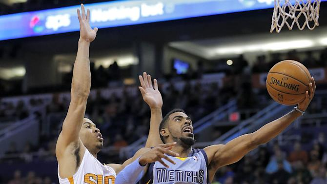 Memphis Grizzlies' Mike Conley (11) shoots past Phoenix Suns' Gerald Green during the first half of an NBA basketball game on Thursday, Jan. 2, 2014, in Phoenix
