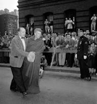 FILE - In this April 1957 file photo, Boston Athletic Association trainer Jock Semple walks a blanket-wrapped John J. Kelley after Kelley won the Boston Marathon in Boston. Kelley, known to his fans as the first modern American road runner, has died. Amby Burfoot, a friend whom Kelley coached in high school in Groton in the early 1960s, confirmed his death. He said Kelley died Sunday, Aug. 21, 2011, in Stonington, Conn., at his daughter's home from a melanoma that spread to his lungs. He was 80. (AP Photo)