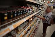 A woman choses sweets at a counter with imported food stuffs at a supermarket in downtown Moscow on Thursday, Aug. 7, 2014.The Russian government has banned all imports of meat, fish, milk and milk products and fruit and vegetables from the United States, the European Union, Australia, Canada and Norway, Prime Minister Dmitry Medvedev announced Thursday. The move was taken on orders from President Vladimir Putin in response to sanctions imposed on Russia by the West over the crisis in Ukraine. The ban has been introduced for one year. (AP Photo/Ivan Sekretarev)