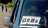 A placard issued by French gendarmerie forces showing four wanted illegal gold miners, including Manoel Ferreira Mourra (2nd L), is seen on a car windscreen, on July 18, in Dorlin, on the road between Cayenne and Regina, in the overseas territory of French Guiana