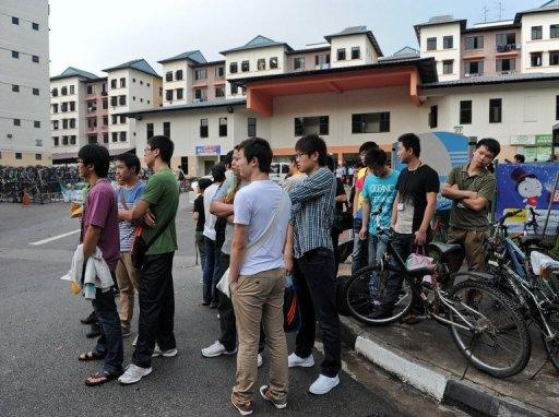 Foreign workers wait for their transportation to work outside their dormitory in Singapore on November 26. Four mainland Chinese bus drivers accused of instigating Singapore's first strike since the 1980s were charged on Thursday with criminal offences that could land them in prison