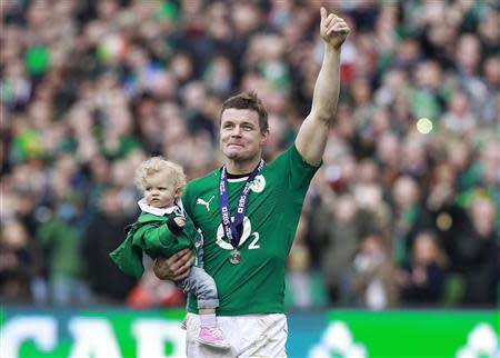 Ireland's O'Driscoll waves to spectators as he carries his daughter Sadie at the end of the Six Nations rugby union match against Italy at Aviva stadium in Dublin