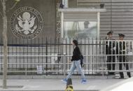 A woman walks past paramilitary police officers standing guard outside the U.S. embassy in Beijing