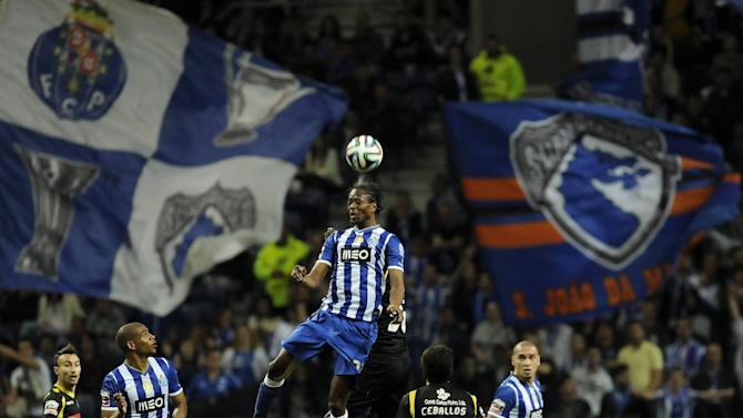 FC Porto's Abdoulaye Ba, center, from Senegal challenges for a high ball with Arouca's Salim Cisse, from Guinea Conakry, in a Portuguese League soccer match at the Dragao stadium, in Porto, Portugal, Sunday, March 9, 2014