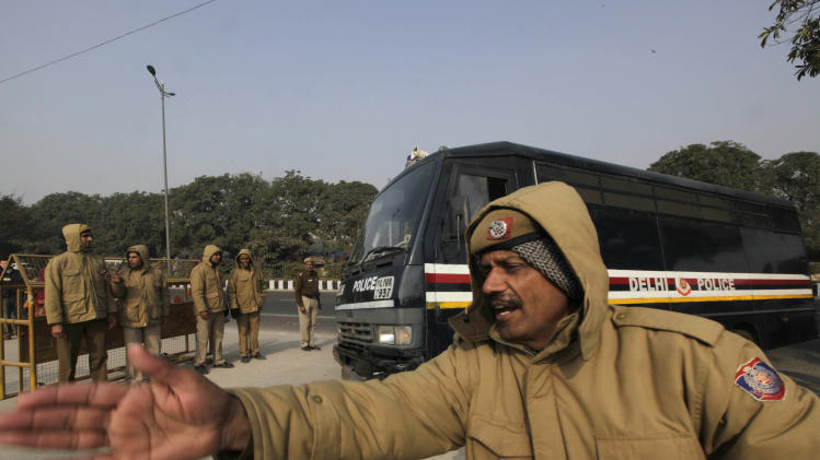 A police officer clears the way for a police van believed to carrying five men accused in a gang rape as they arrive at the district court, in New Delhi, India, Monday, Jan. 7, 2013. The men, who were set to appear in court Monday, are accused of the Dec. 16 gang rape on a woman, who later died of her injuries, that has caused outrage across India, sparking protests and demands for tough new rape laws. (AP Photo/Manish Swarup)