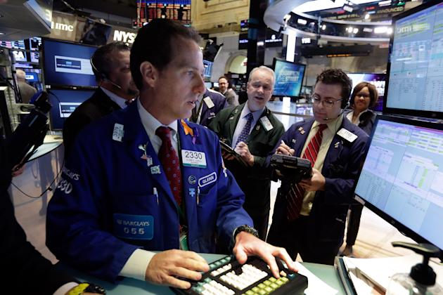 Specialist Glenn Carell, left, works with traders at the post that handles Alibaba, on the floor of the New York Stock Exchange Wednesday, March 4, 2015. U.S. stocks are opening lower, putting the mar
