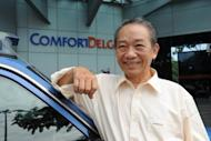 Taxi driver Sia Ka Tian stands next to his taxi in front of the transport company in Singapore. Sia returned Sg$1.1 million ($900,000) in cash to a vacationing Thai couple who left the money in his cab on November 19, 2012 and received an undisclosed reward