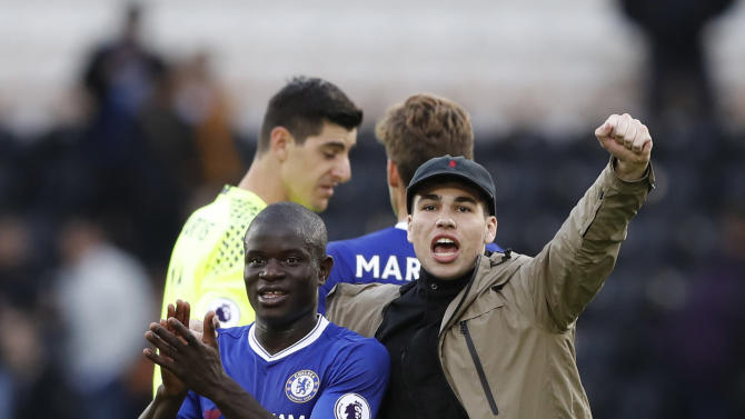 A pitch invader runs on to the pitch and celebrates with Chelsea's N'Golo Kante at full time