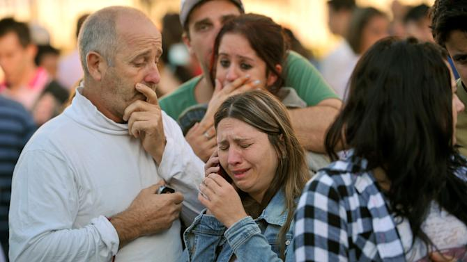 Relatives of victims react as they wait for news in fron of the Kiss nightclub in Santa Maria city,  Rio Grande do Sul state, Brazil, Sunday, Jan. 27, 2013.  According to police more than 200 died in the devastating nightclub fire in southern Brazil.  Officials say the fire broke out at the club while a band was performing. (AP Photo/Ronald Mendes-Agencia RBS)