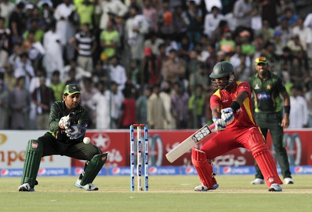 Zimbabwe's Chibhabha plays a shot next to Pakistan's wicketkeeper Ahmed during their second One Day International cricket match at the Gaddafi Cricket Stadium in Lahore