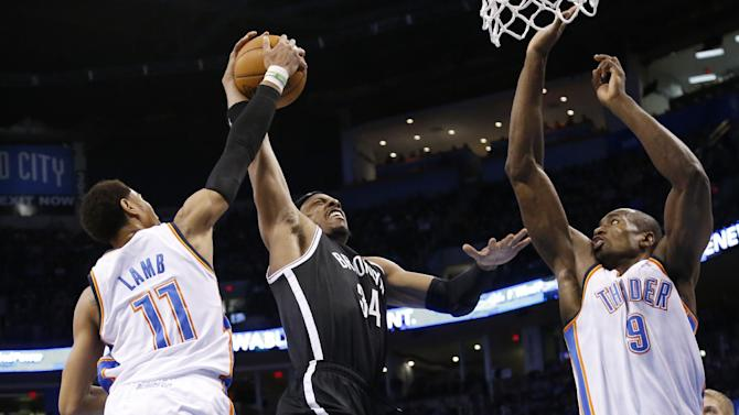 Oklahoma City Thunder guard Jeremy Lamb (11) blocks a shot by Brooklyn Nets forward Paul Pierce (34) as Pierce shoots between Lamb and forward Serge Ibaka (9) in the second quarter of an NBA basketball game in Oklahoma City, Thursday, Jan. 2, 2014