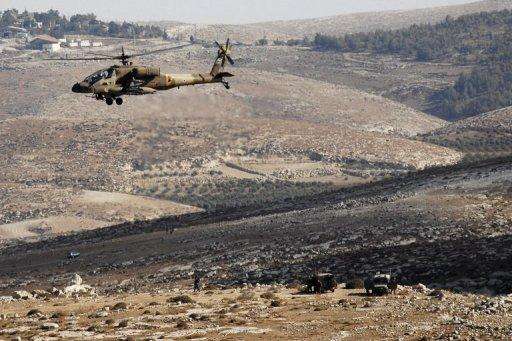 "An Israeli army helicopter hovers over the Hebron hills in the West Bank. Three Israeli settlers in the West Bank were on Thursday charged in Beersheva district court with carrying out a ""price-tag"" attack against Palestinian property, the justice ministry said"
