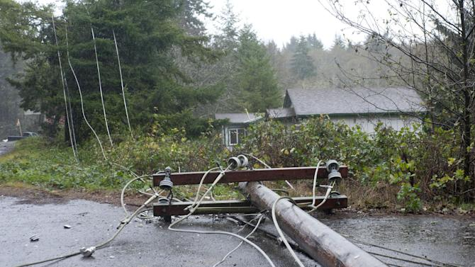Utility pole and lines lie on the road north of Lincoln City, Ore., Monday Nov. 19, 2012 after being felled by trees knocked down by high winds.   A storm bearing down on the Pacific Northwest has taken the life of an elk hunter on the Oregon Coast and hit the region with mudslides, high winds and mountain snow.  (AP Photo/The Oregonian, Brent Wojahn)