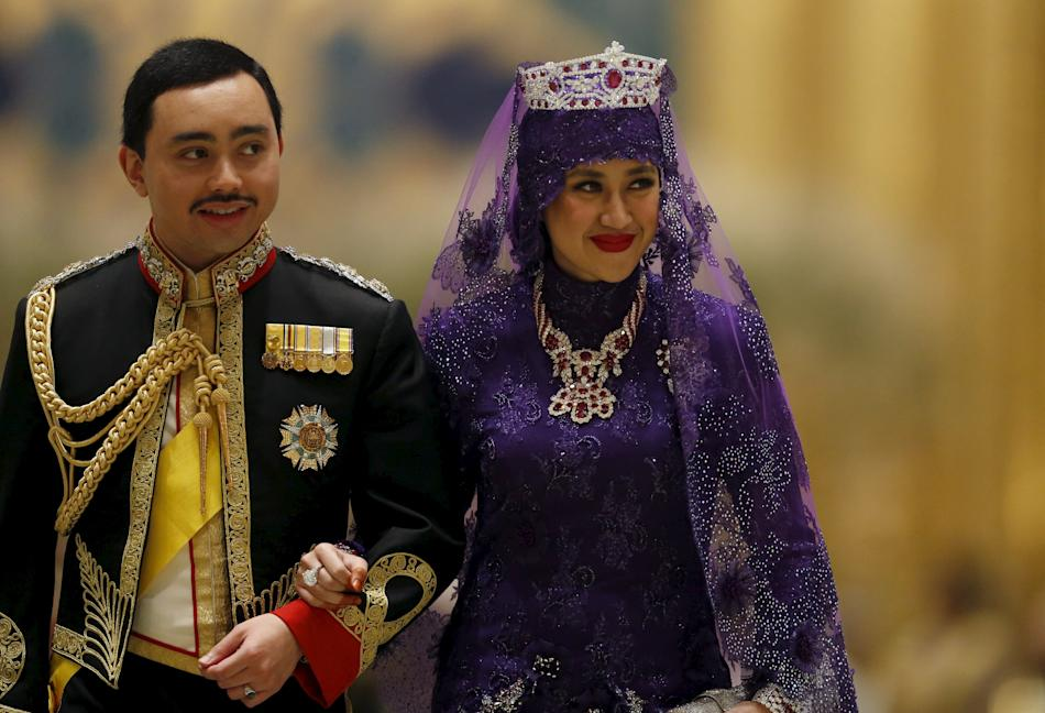Brunei's newly wed royal couple, Prince Abdul Malik and Dayangku Raabi'atul 'Adawiyyah Pengiran Haji Bolkiah, leave the royal wedding banquet at the Nurul Iman Palace in Bandar Seri Begawa