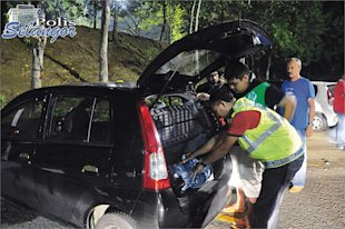 Police officers thoroughly checking a vehicle during a major operation at an undisclosed location in Selangor yesterday.