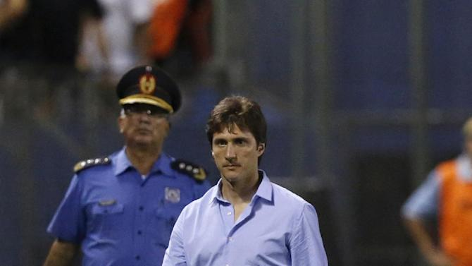 Guillermo Barros Schelotto, coach of Argentina's Lanus, walks at half time during a Copa Sudamericana soccer game with Paraguay's Libertad in Asuncion, Paraguay, Thursday, Nov. 21, 2013