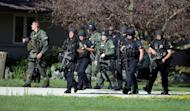 Law enforcement personnel walk near the Sikh Temple of Wisconsin where a gunman attacked worshipers killing at least six people before he was himself shot dead by police