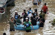 Volunteers use rubber a boat to ferry residents to safer grounds following a flash flood that inundated Cagayan de Oro city, Philippines, Saturday, Dec. 17, 2011. A tropical storm triggered flash floods in the southern Philippines, killing scores of people and missing more. Mayor Lawrence Cruz of nearby Iligan said the coast guard and other rescuers were scouring the waters off his coastal city for survivors or bodies that may have been swept to the sea by a swollen river. (AP Photo/Froilan Gallardo)