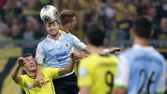 Munich's Moritz Stoppelkamp, top, and Dortmund's Nuri Sahin of Turkey challenge for the ball during the German soccer cup second round match between TSV 1860 Munich and Borussia Dortmund, in Munich, southern Germany, Tuesday, Sept. 24, 2013