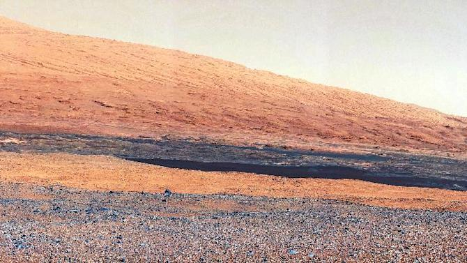 "In this image released by NASA on Monday, Aug. 27, 2012, a photo taken by the Mast Camera (MastCam) highlights the geology of Mount Sharp, a mountain inside Gale Crater, where the rover landed. Prior to the rover's landing on Mars, observations from orbiting satellites indicated that the lower reaches of Mount Sharp, below the line of white dots, are composed of relatively flat-lying strata that bear hydrated minerals. Those orbiter observations did not reveal hydrated minerals in the higher, overlying strata. The MastCam data now reveal a strong discontinuity in the strata above and below the line of white dots, agreeing with the data from orbit. Strata overlying the line of white dots are highly inclined (dipping from left to right) relative to lower, underlying strata. The inclination of these strata above the line of white dots is not obvious from orbit. This provides independent evidence that the absence of hydrated minerals on the upper reaches of Mount Sharp may coincide with a very different formation environment than lower on the slopes. The train of white dots may represent an ""unconformity,"" or an area where the process of sedimentation stopped. (AP Photo/NASA/JPL-Caltech/MSSS)"