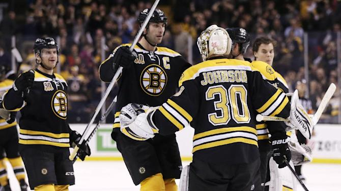 Boston Bruins goalie Chad Johnson (30) is congratulated by teammates after their 3-2 overtime win against the Columbus Blue Jackets in an NHL hockey game, in Boston, Thursday, Nov. 14, 2013. The Bruins defeated the Blue Jackets 3-2