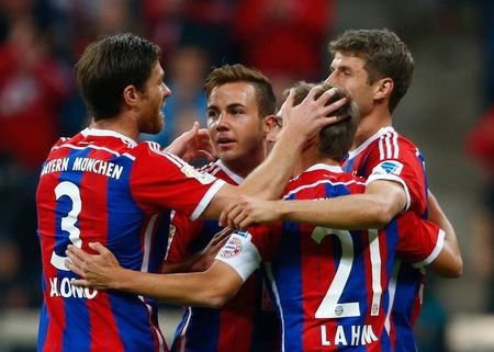 Bayern Munich's Xabi Alonso, Mario Goetze, Philipp Lahm and Thomas Mueller (L-R) celebrate after Goetze scored a goal against Paderborn during their German first division Bundesliga match in Munich September 23, 2014.  REUTERS/Michael Dalder
