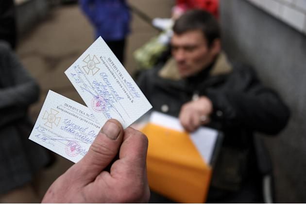 In a picture taken on March 2, 2015, a man holds permits to cross from Ukraine to rebel held territory in the town of Velyka Novosilka, Ukraine. Restrictions imposed on travel from separatist-controll
