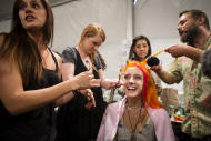 A model has her hair done backstage before the Nicole Miller Spring 2013 collection is modeled during Fashion Week in New York, Friday, Sept. 7, 2012. (AP Photo/John Minchillo)