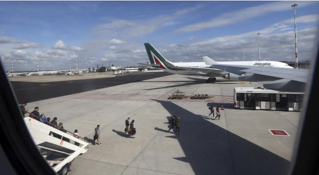 FILE -- In this Nov. 4, 2013 file photo, passengers disembark from an Alitalia plane at the Fiumicino airport in Rome.  Italy's flagship airline Alitalia called disrespectful of passengers a 24-ho