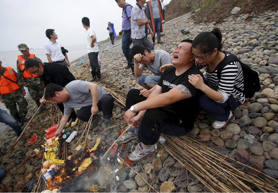 Family members of Eastern Star cruise ship victims burn offerings as they cry during a ceremony to mark seven days since the ship went down in the Jianli section of Yangtze River