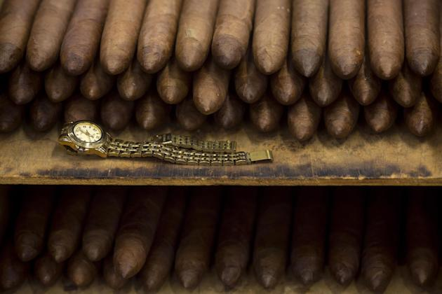 In this Feb. 26, 2015 photo, an employee's watch sits next to a stack of cigars at the Corona cigar factory in Havana, Cuba. Cuban cigar makers are licking their chops over new U.S. rules that let