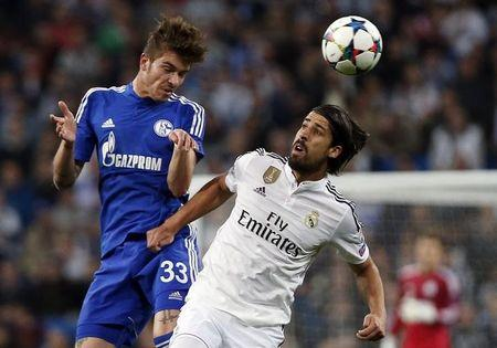 Real Madrid's Sami Khedira is challenged by Schalke 04's Roman Neustadter during their round of 16 second leg soccer match in Madrid