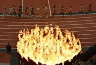 Athletes run past the Olympic Flame as they compete in the women's 10,000m final at the athletics event during the London 2012 Olympic Games on August 3, 2012 in London