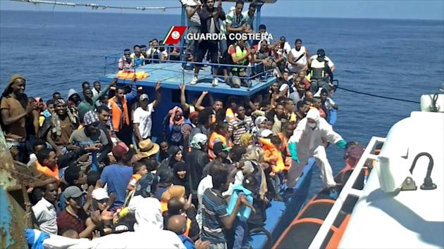 Migrants wait to be rescued from an overcrowded boat off the coast of Libya on August 23, 2015