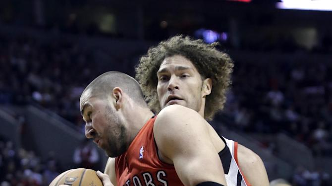 Toronto Raptors center Jonas Valanciunas, left, makes a drive on Portland Trail Blazers center Robin Lopez during the first half of an NBA basketball game in Portland, Ore., Saturday, Feb. 1, 2014