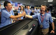 MSL Flight director Keith Comeaux (R) celebrates with Martin Greco after a successful landing for the Curiosity rover